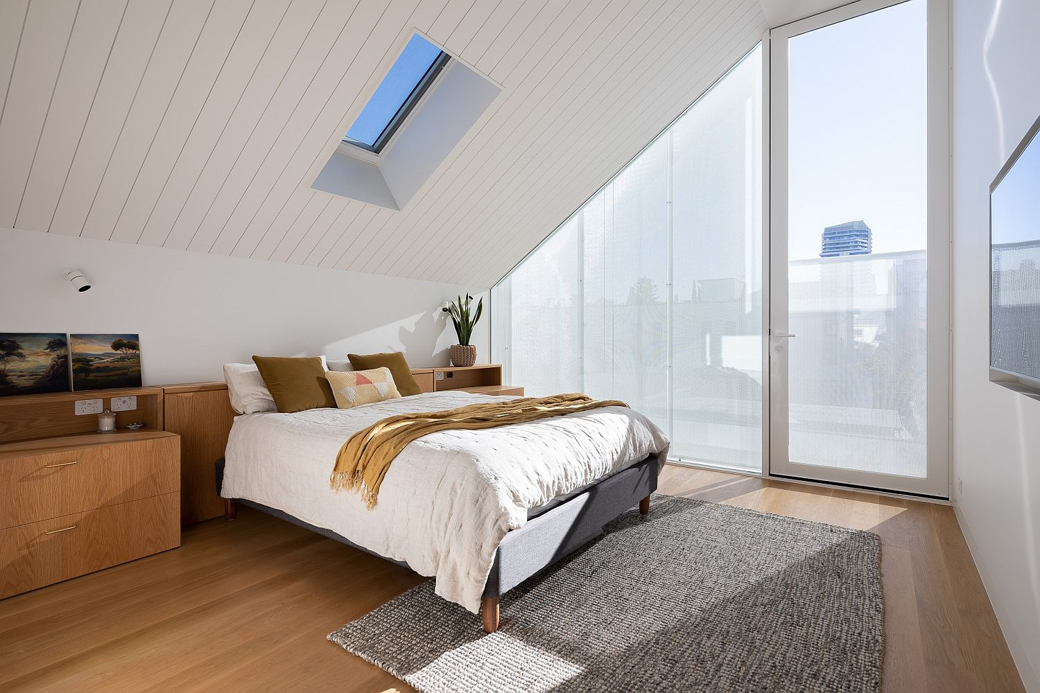Bedroom with slanting ceiling, skylight and glass walls feels spacious and modern