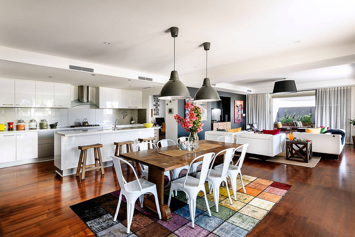 Bright multi-colored rug and oversized pendant lights for the modern dining room next to the kitchen