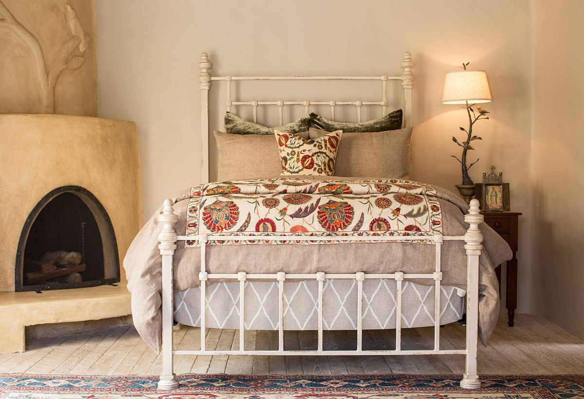 Charming little bedroom with fireplace in the corner, wrought iron bed and cozy ambiance