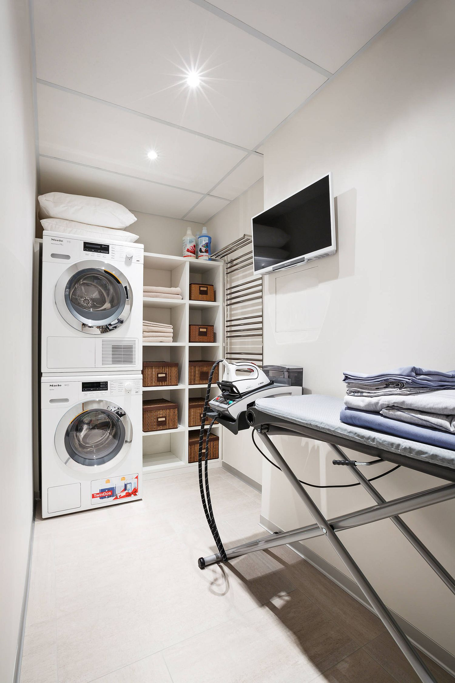 laundry room featuring television above ironing area