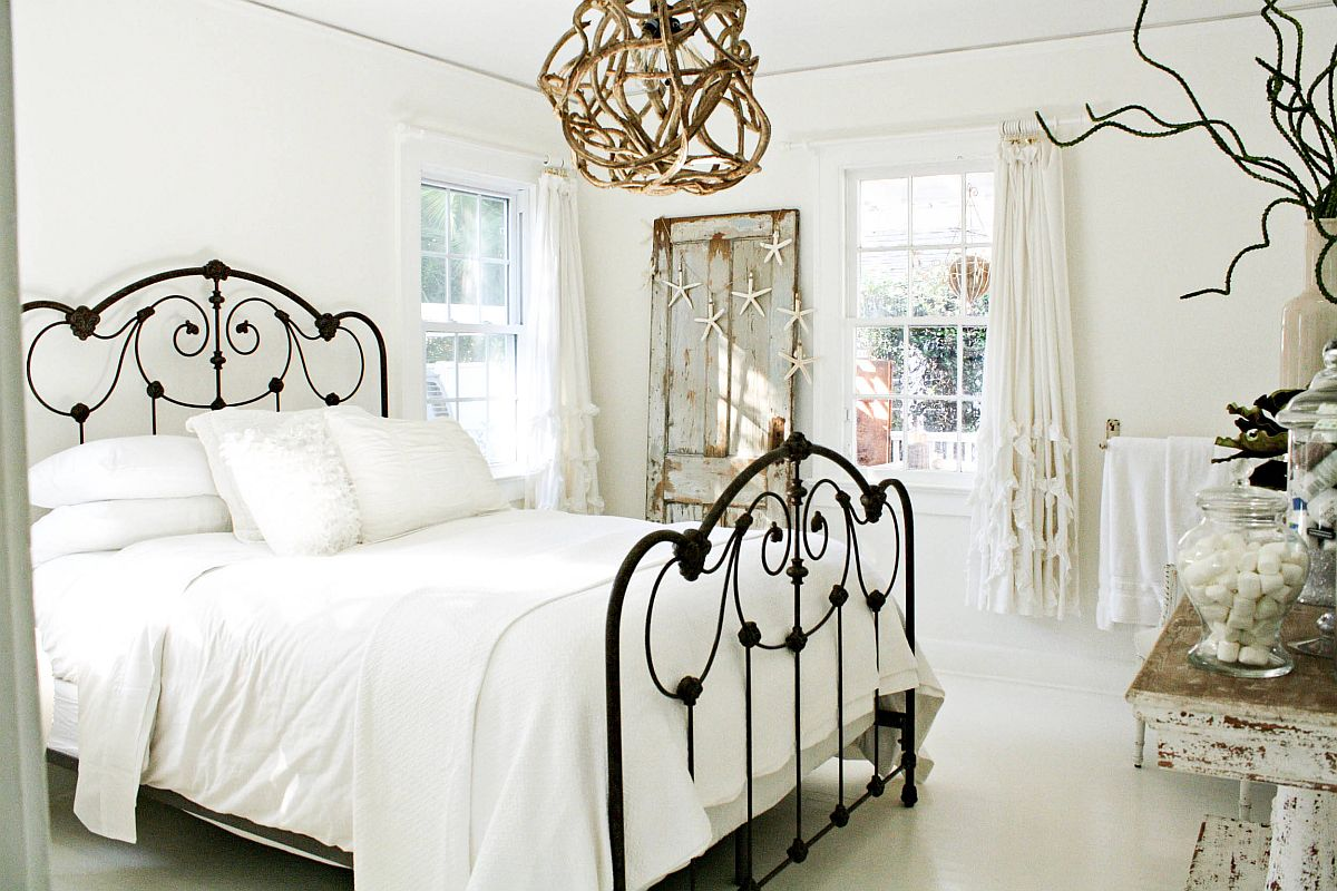 Coastal and shabby chic styles coupled in the white bedroom with wrought iron frame