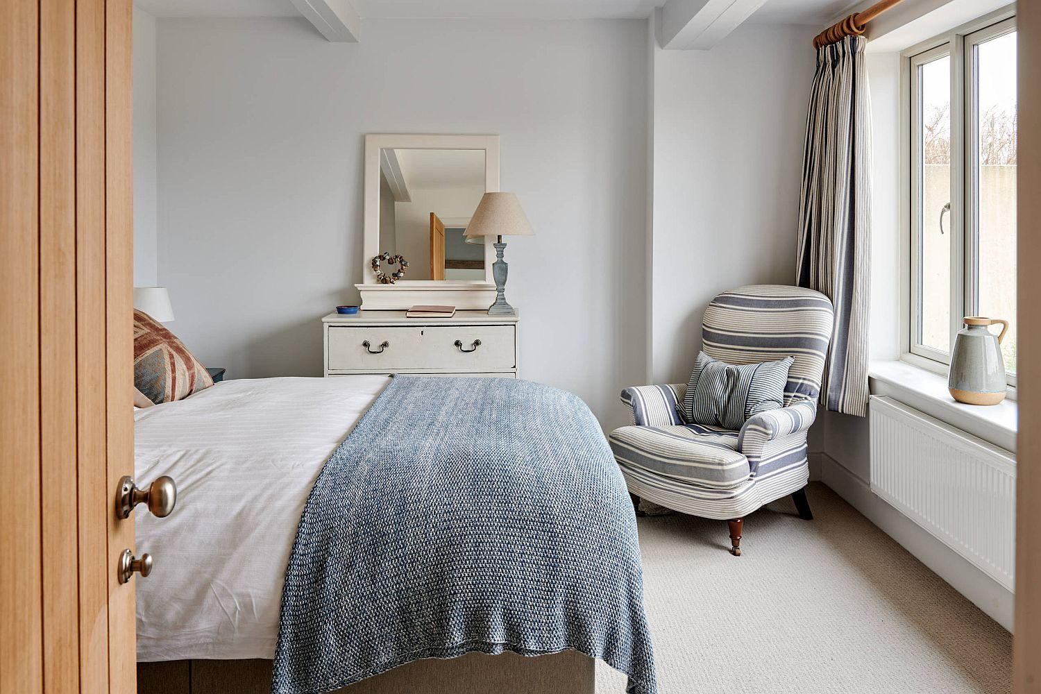 Comfy chair in the corner adds additional sitting space in the small bedroom