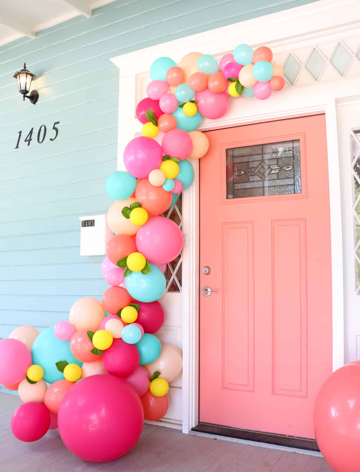 Coral front door with a balloon garland