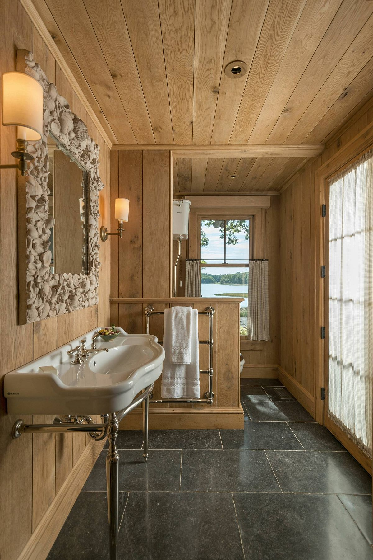 Custom mirror frame for the small rustic bathroom fetauring wood walls and stone flooring