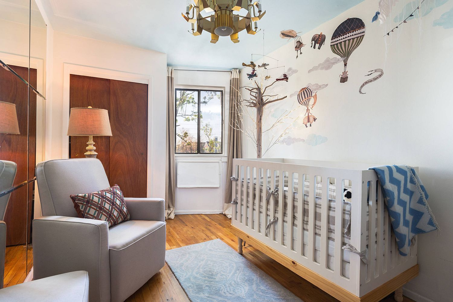 Custom wall decal in the backdrop makes for an interesting visual in the small eclectic nursery with ample natural light
