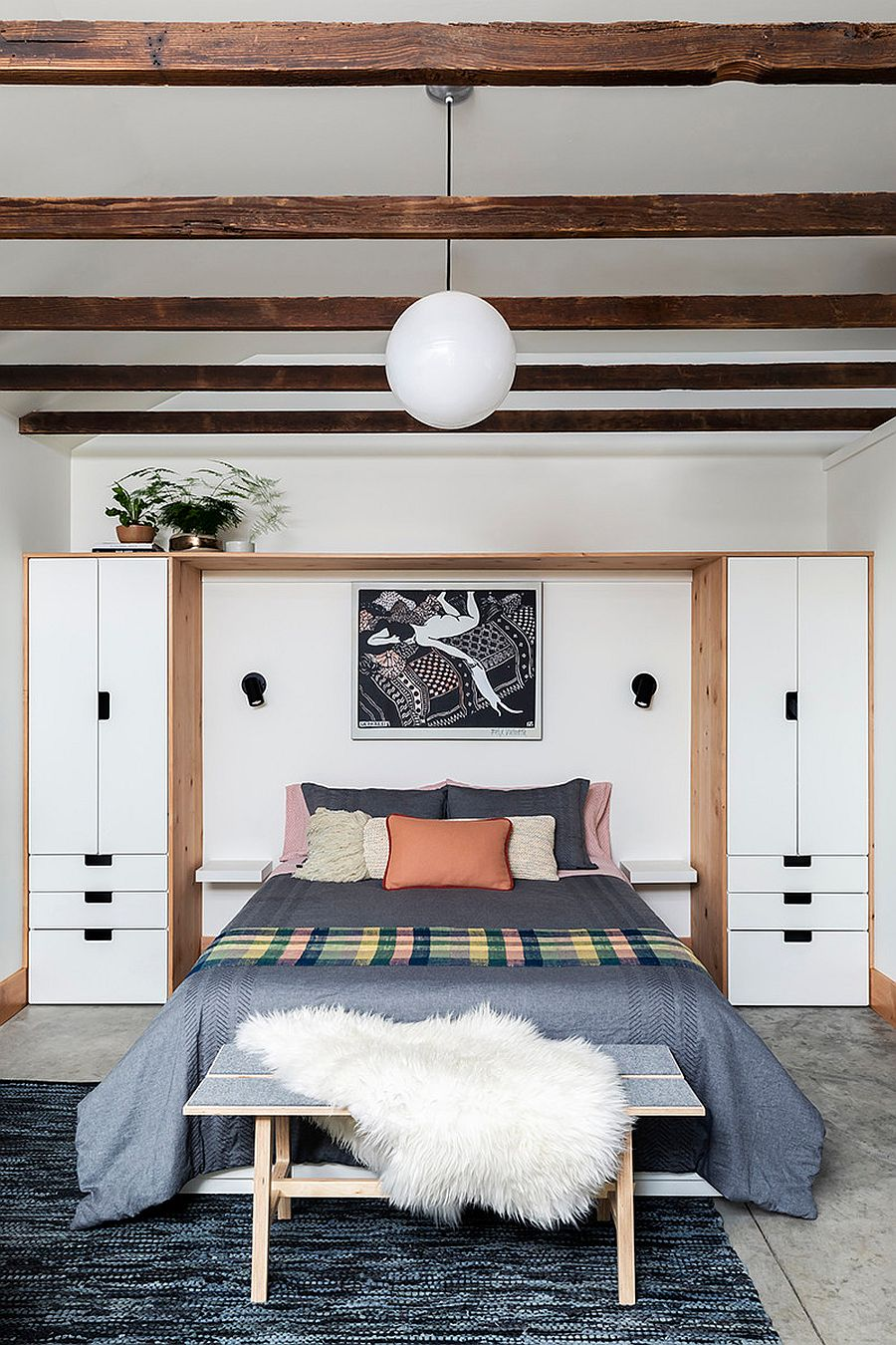Custom white and wood bedroom wardrobe unit saves space in the small interior