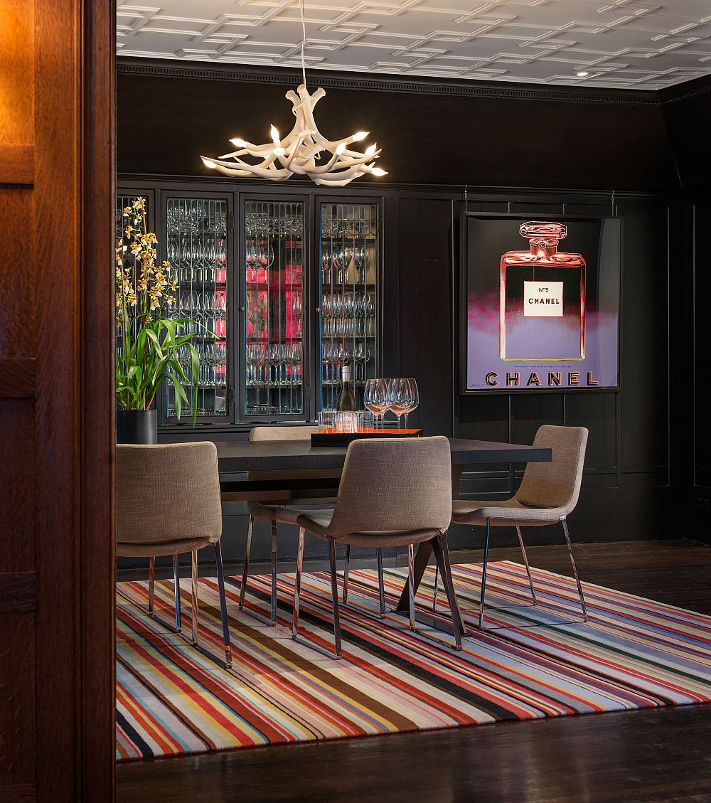 Dark and sophisticated dining room with custom lighting and a brilliant, eye-catching rug