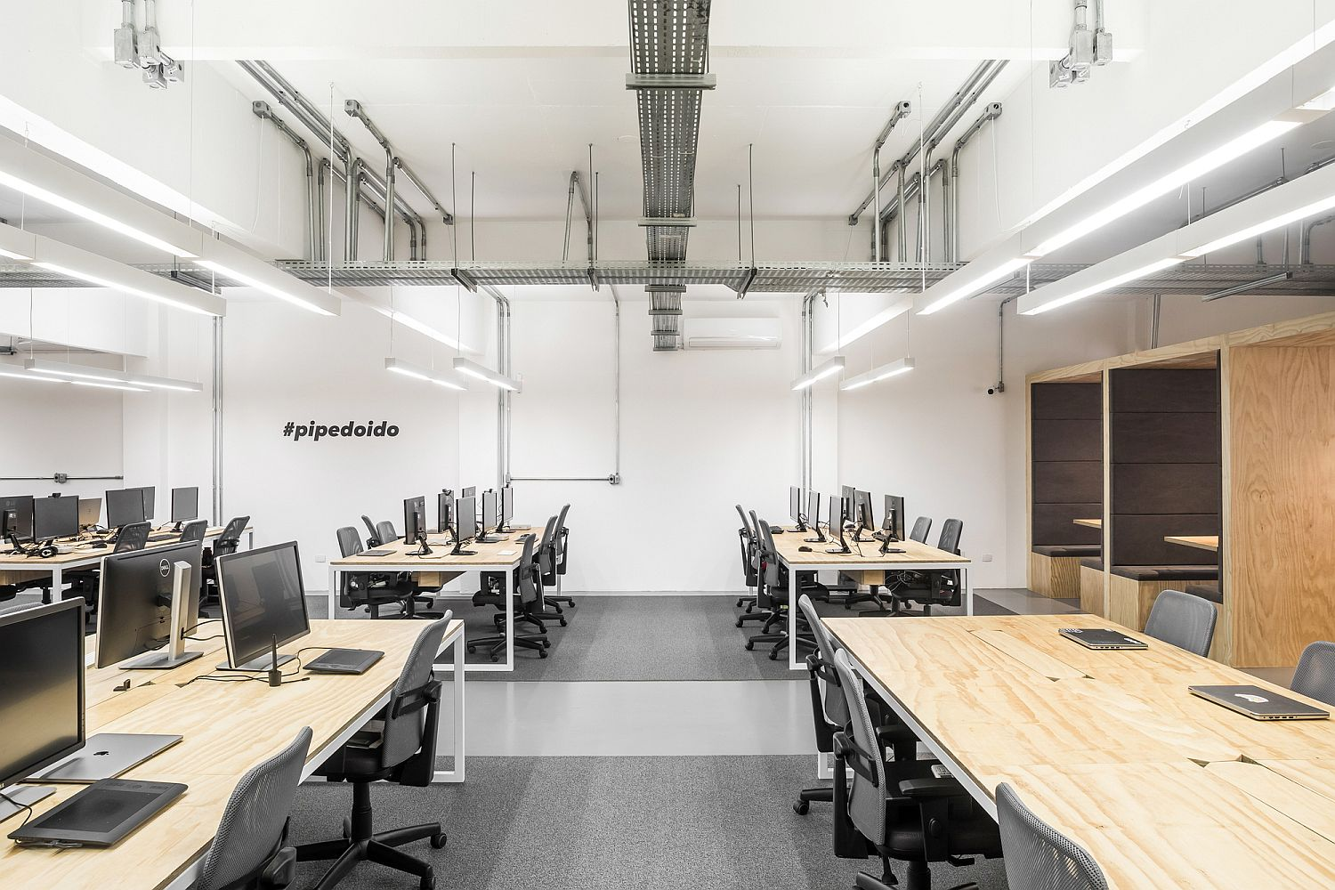 Exposed duct pipes and the flooring bring industrial charm to the modern workspace