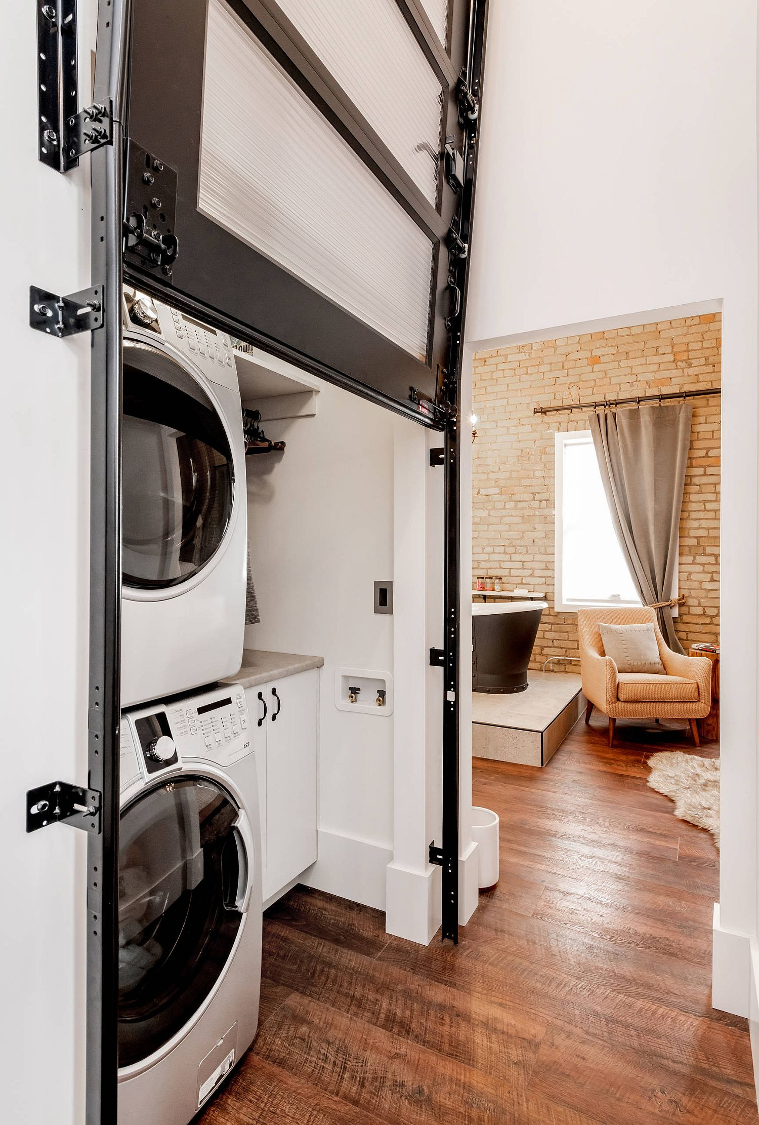 stacked washer and dryer concealed by garage style door