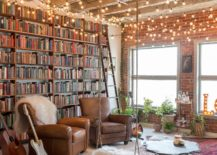 Floor-to-ceiling-bookshelf-with-brick-wall-backdrop-next-to-it-and-brilliant-string-lighting-217x155