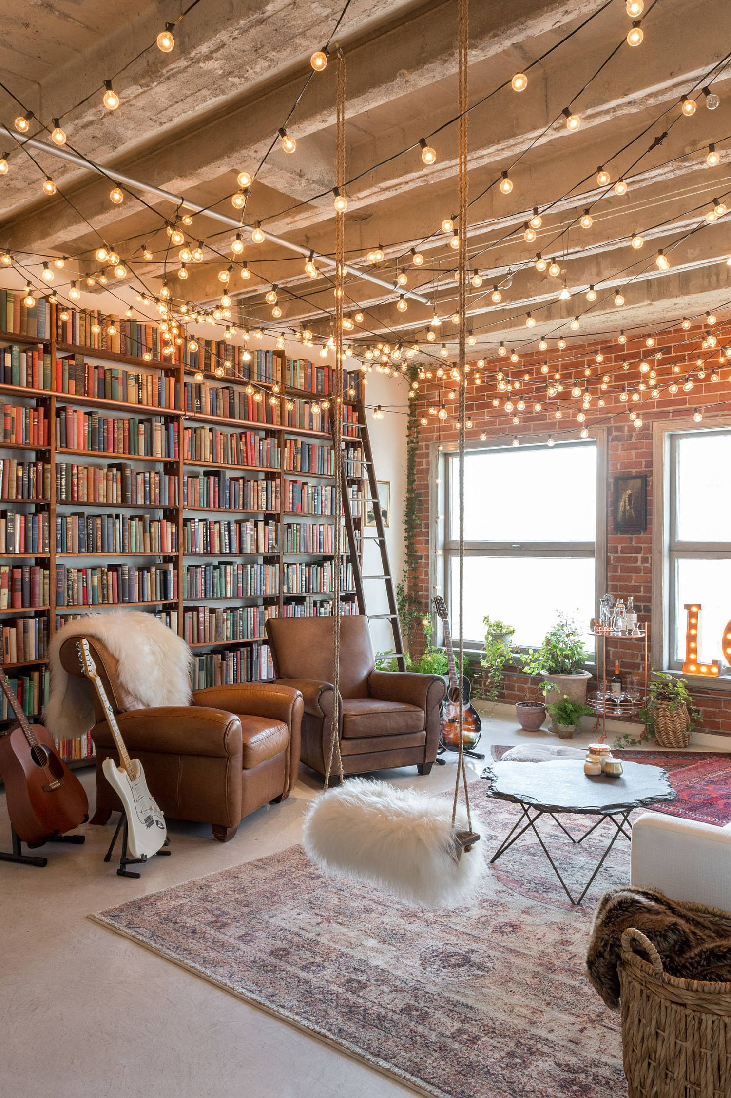 Floor-to-ceiling-bookshelf-with-brick-wall-backdrop-next-to-it-and-brilliant-string-lighting