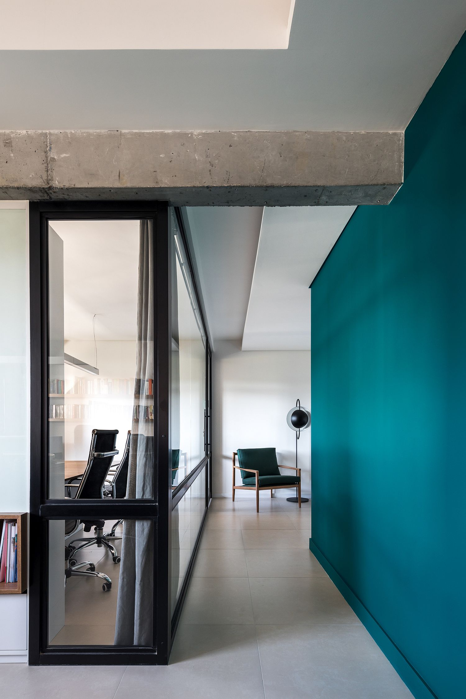 Framed glass walls bring in natural light while the dark green walls hold your attention