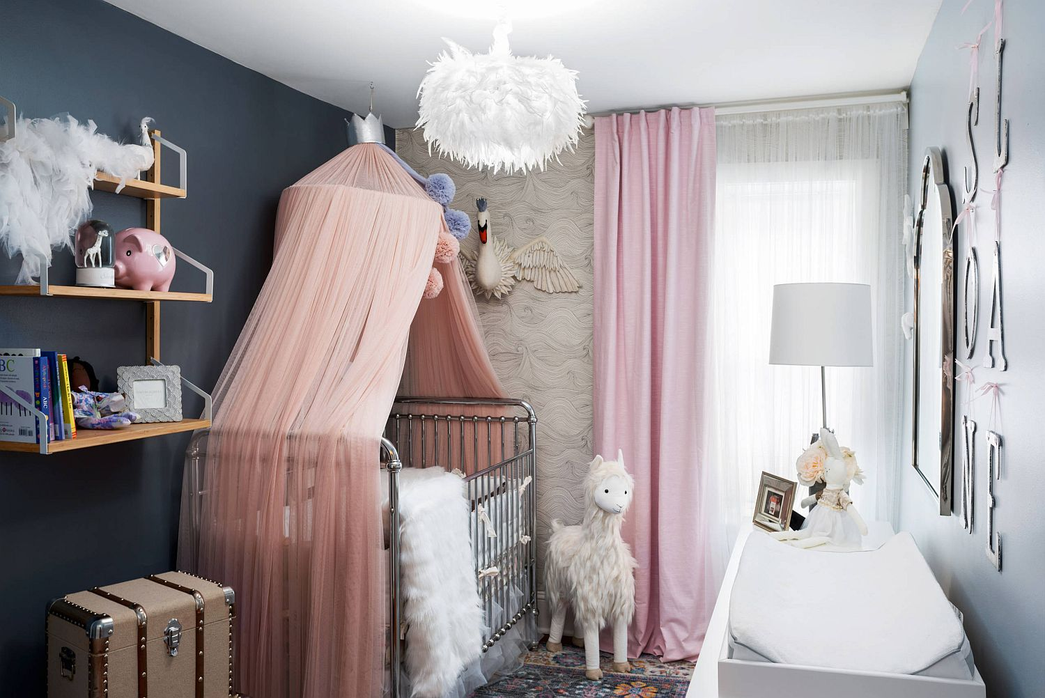 Glam eclectic nursery with pops of pastel pink and bluish-gray in the backdrop