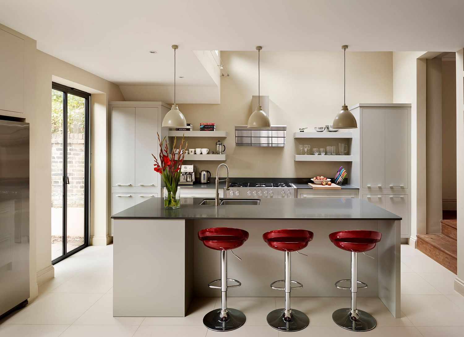 Gorgeous red bar stools feel modern and appropriate in the kitchen despite their bright viusal appeal