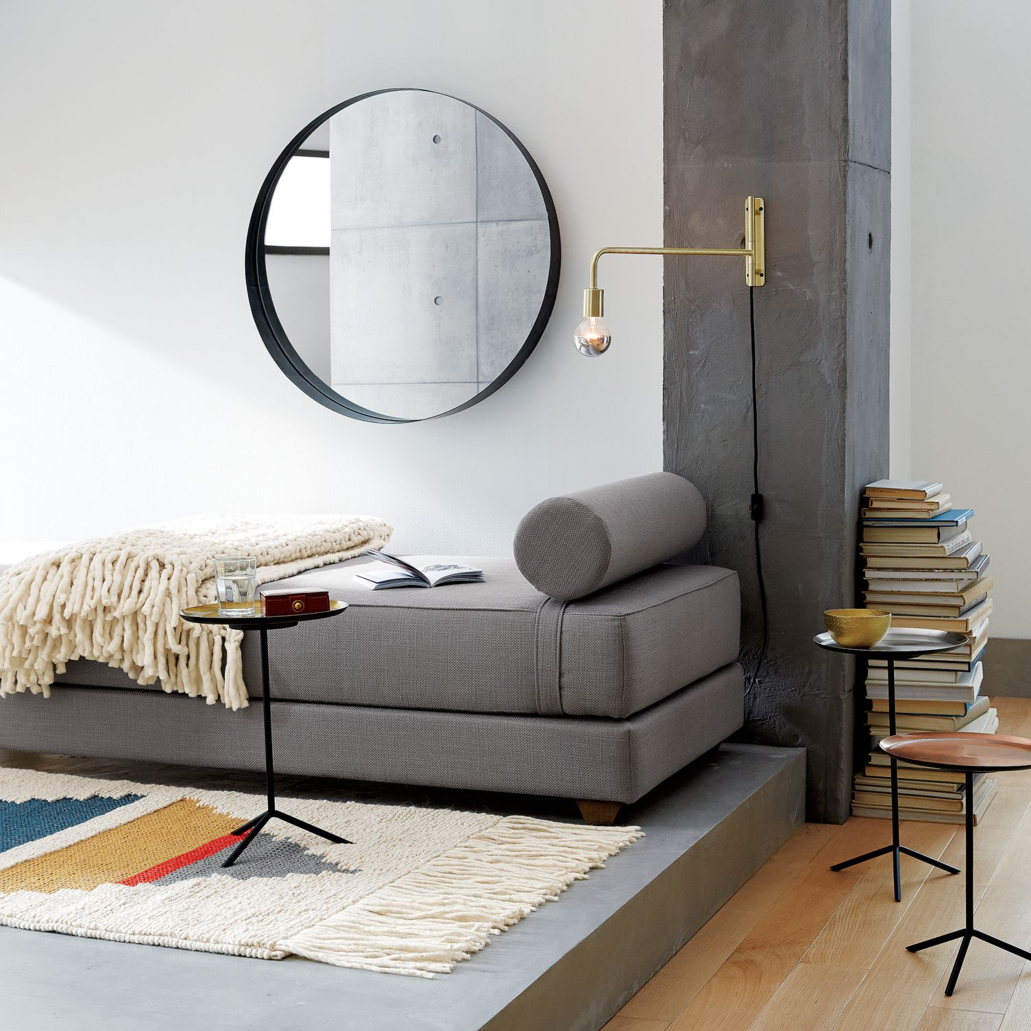 Grey daybed with a cylinder pillow