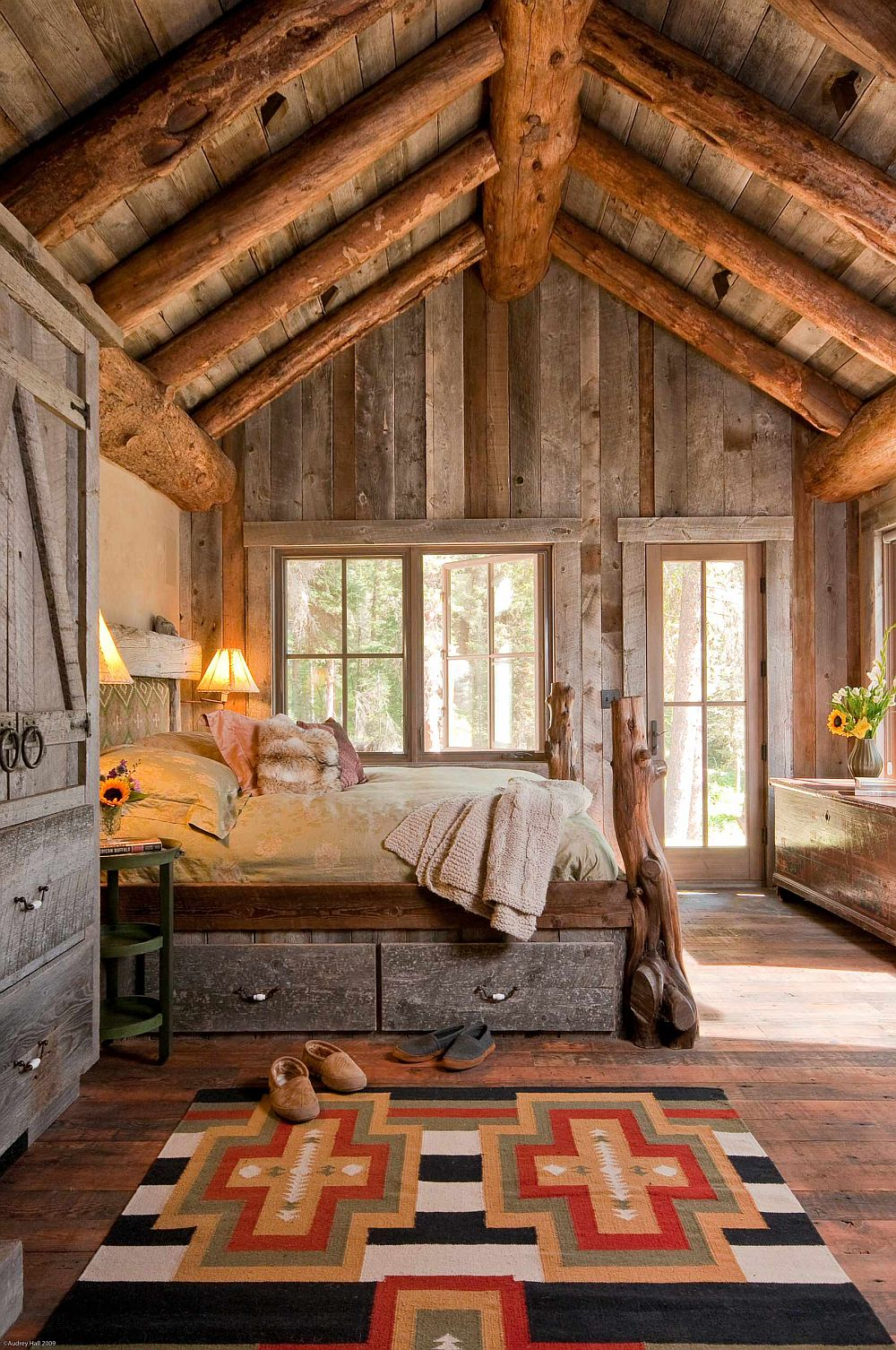 Log-like ceiling beams are perfect for the double-height rustic bedroom in wood