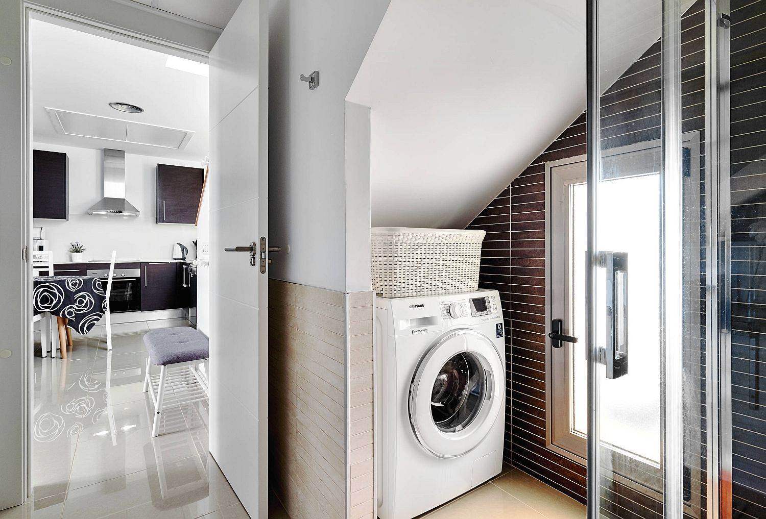 washing machine tucked into corner of bathroom with sloped ceiling