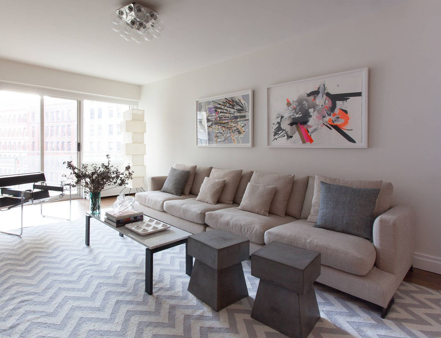 Modern minimal living room in white with chevron pattern flooring and wall art with a dash of color