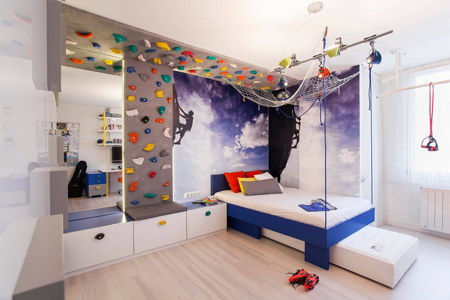 Moving the bed to the corner frees up space in the modern kids' bedroom with climbing wall