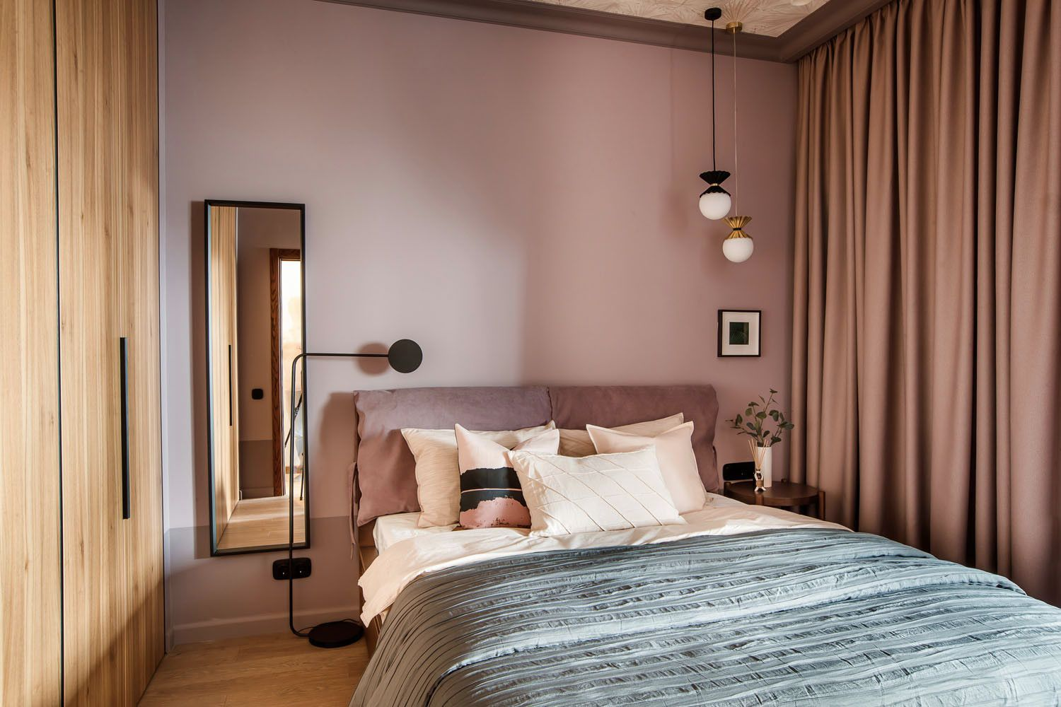 Pastel pink and woodsy cabinet give this modern Scandinavian bedroom a different visual appeal