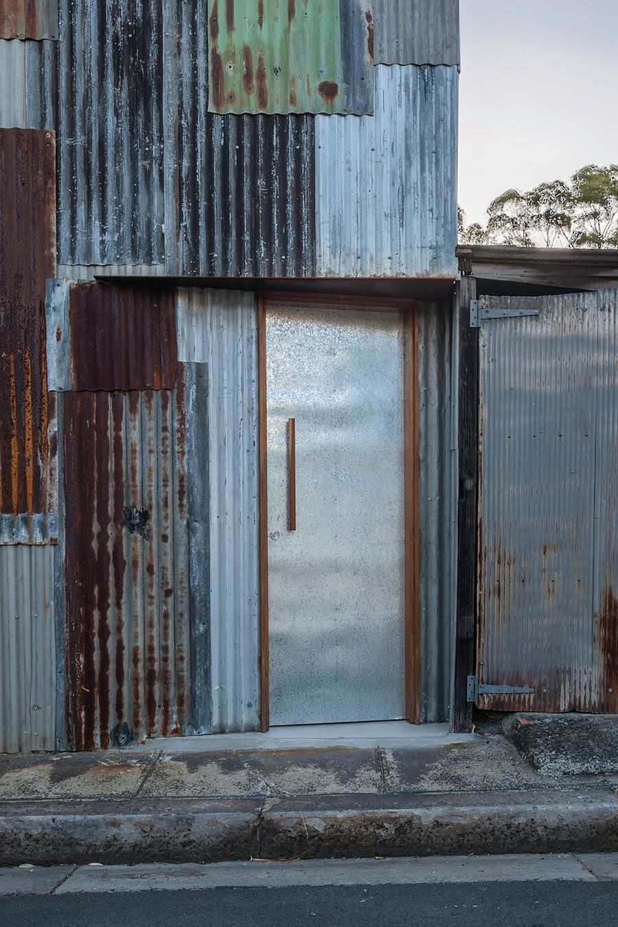 Pieces-from-the-original-disassembled-tin-shed-cover-the-new-facade