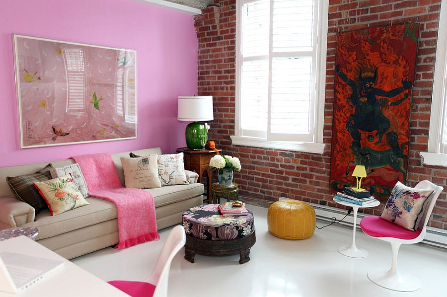 Pops of pink in the eclectic living room with lovely brick wall and colorful wall art