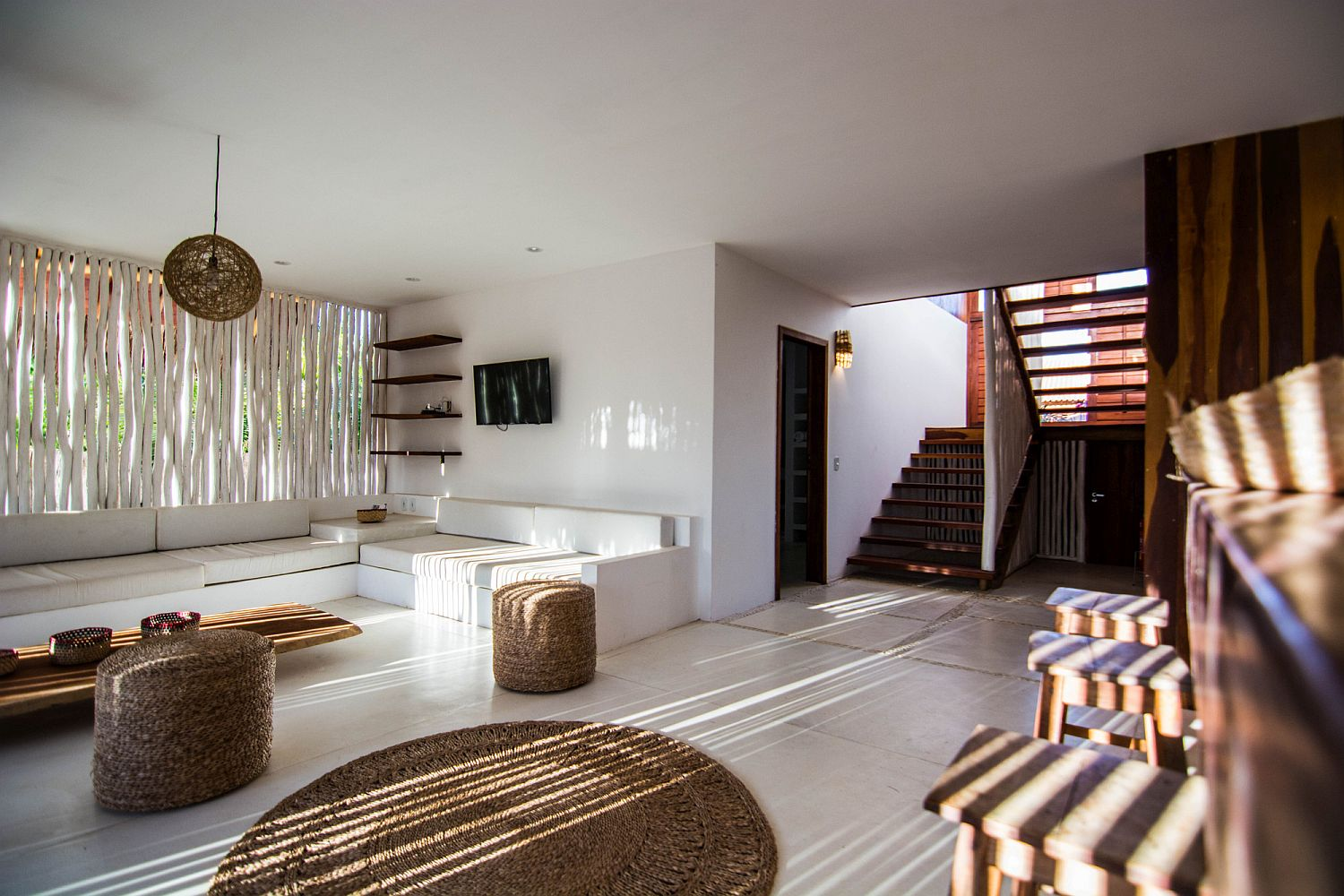 Rattan, wood and bamboo decor inside the all-white vacation home in Brazil