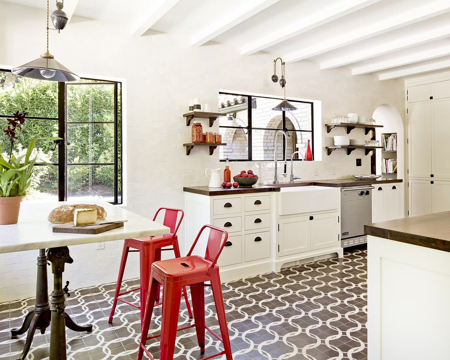 Red bar chairs bring brightness to the small and stylish Mediterranean kitchen in white with lovely floor tiles
