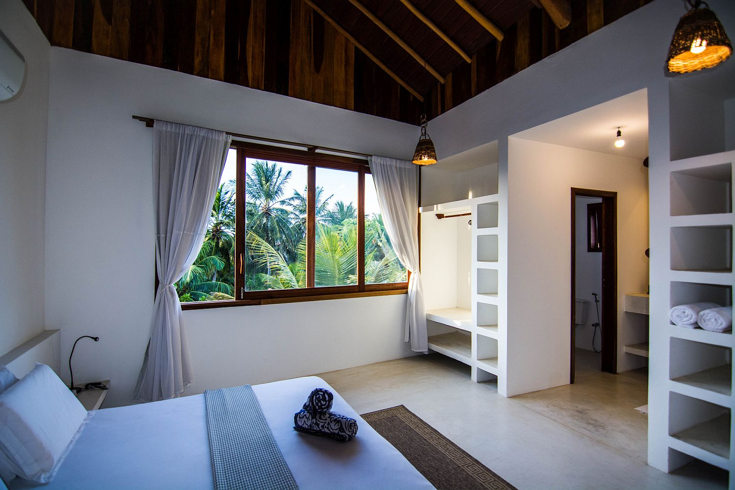 Relaxing and gorgeous bedroom of the holiday house in white with a wooden ceiling