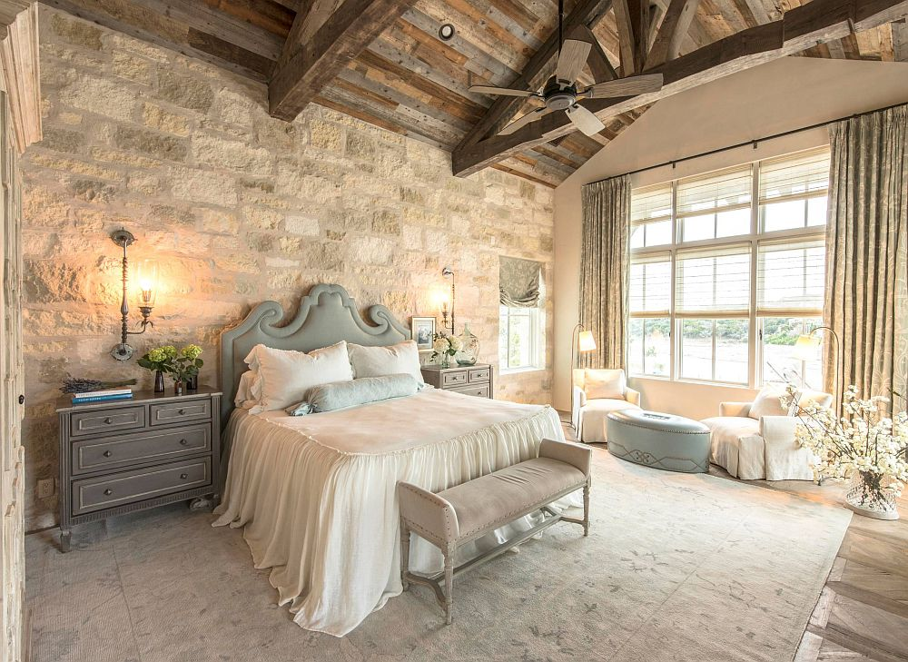 Rustic farmhouse style bedroom has a wooden ceiling and weathered stone walls
