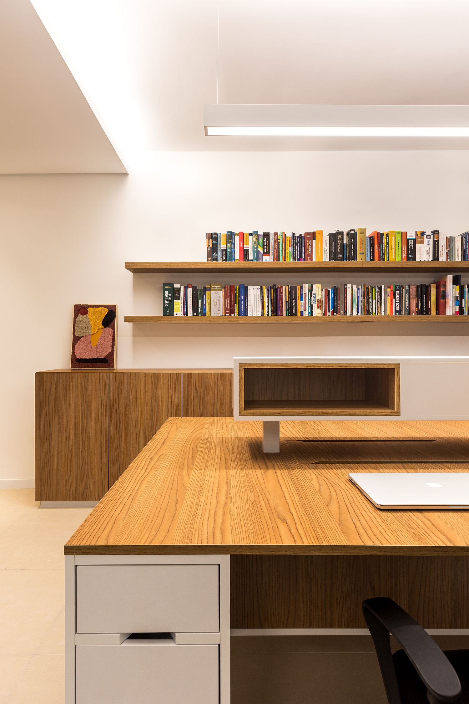 Series of floating wooden shelves hold books and other accessories