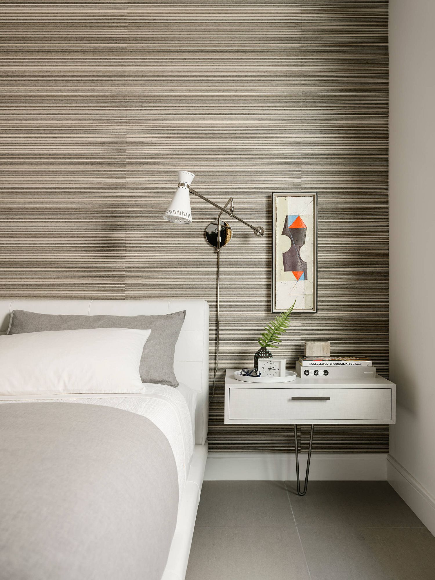 Simple color scheme that uses just two colors and small bedside floating table create a more space-conscious bedroom