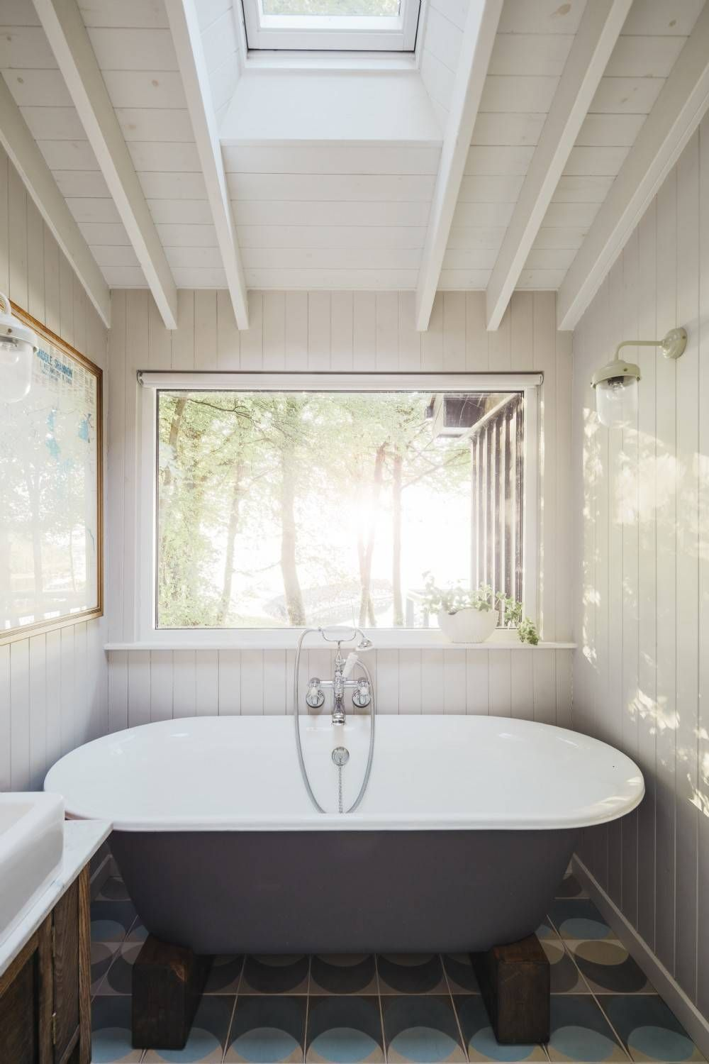 Skylight brings ample natural light into the small bathroom with tiled floor