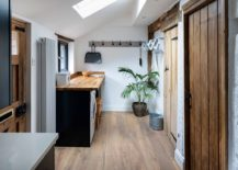 Skylight-slanting-roof-and-natural-woodsy-finishes-give-a-new-life-to-the-laundry-in-white-217x155