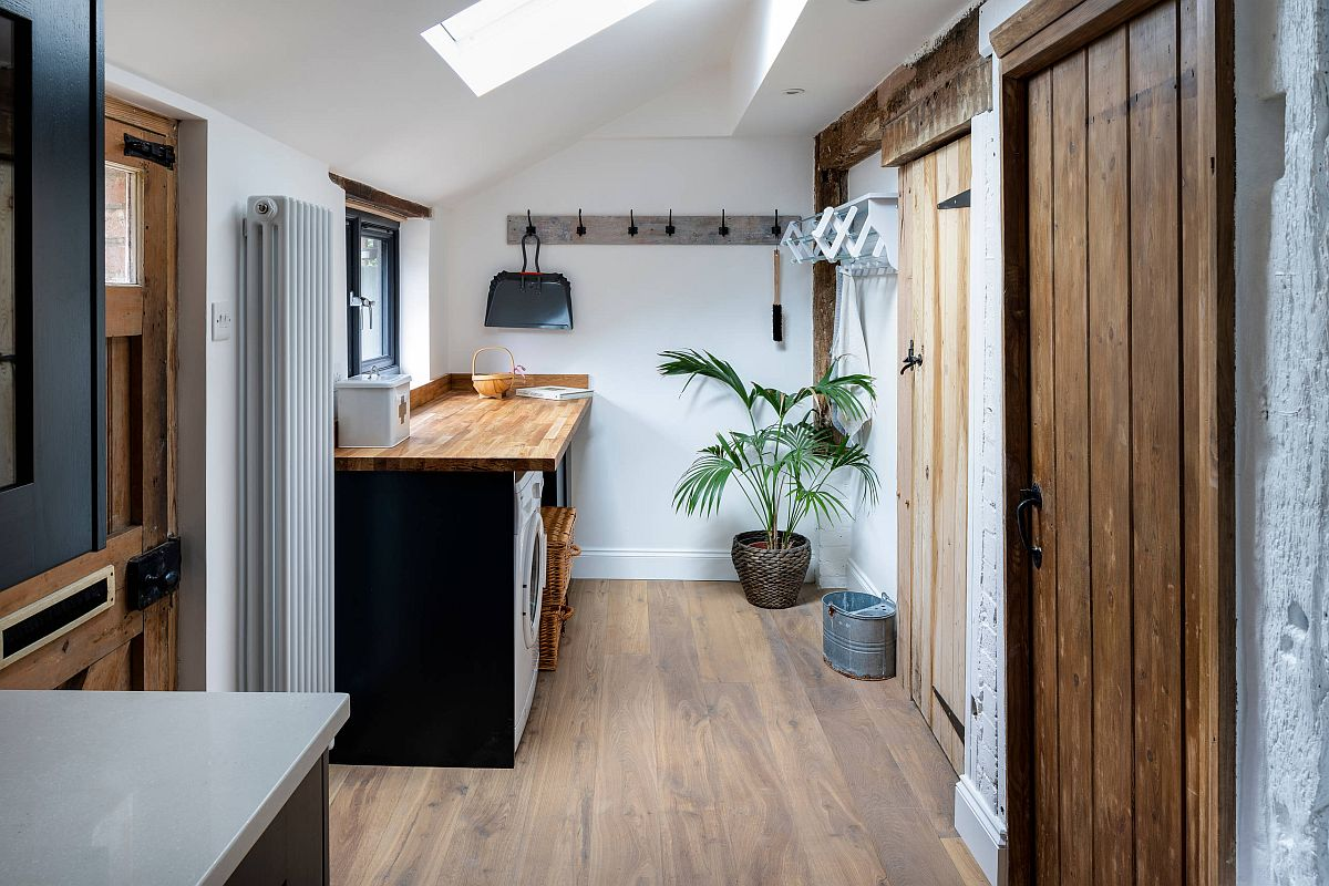 Skylight, slanting roof and natural woodsy finishes give a new life to the laundry in white