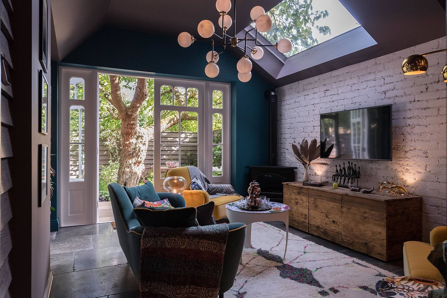 Small eclectic living room with brick wall backdrop, skylights and a view into the world outside