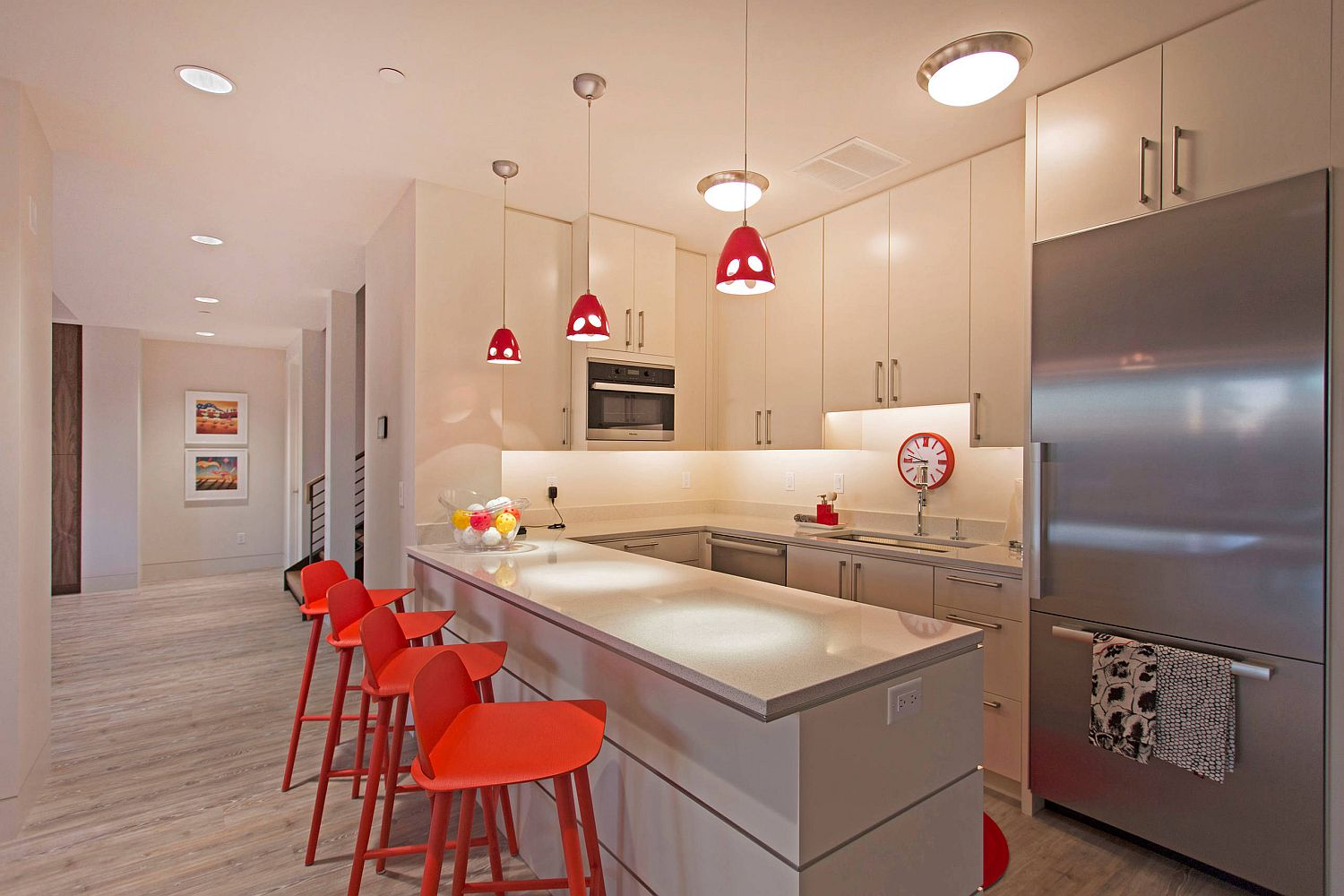 Snazzy red bar stools with geometric charm and pendant lights bring color to this ergonomic modern kitchen