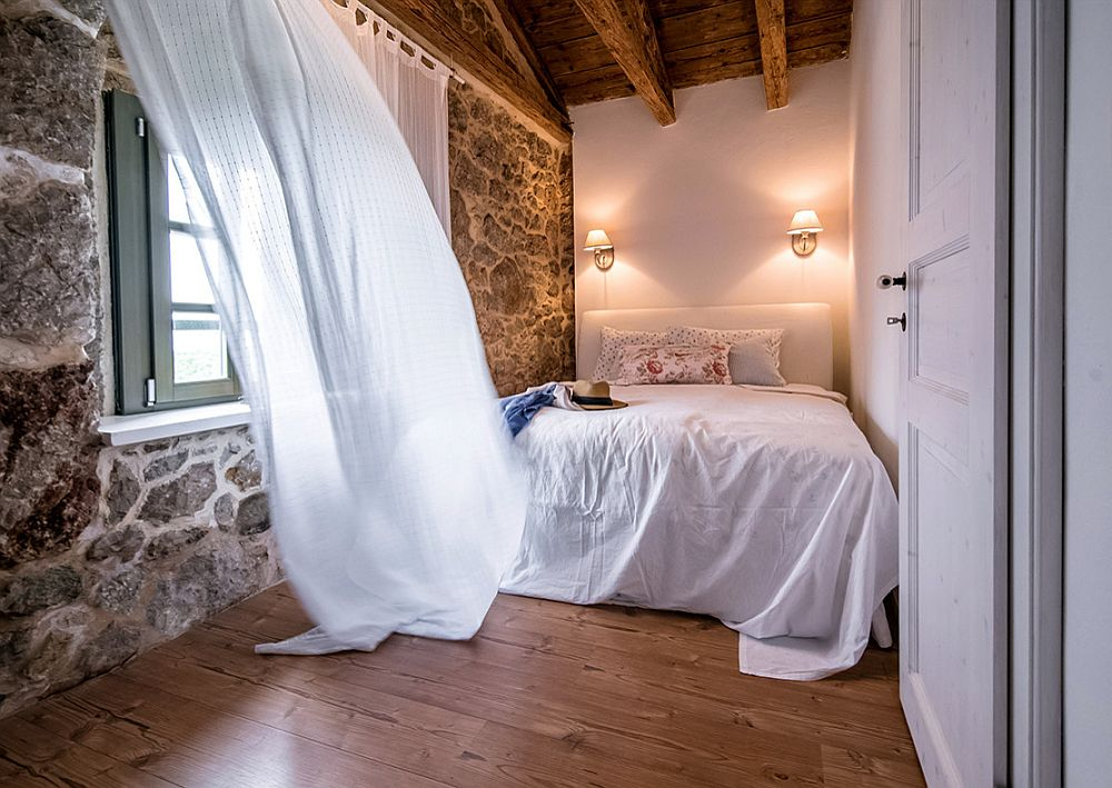 Stone wall and wooden ceiling coupled with white sheer curtains add Mediterranean beauty to the small bedroom
