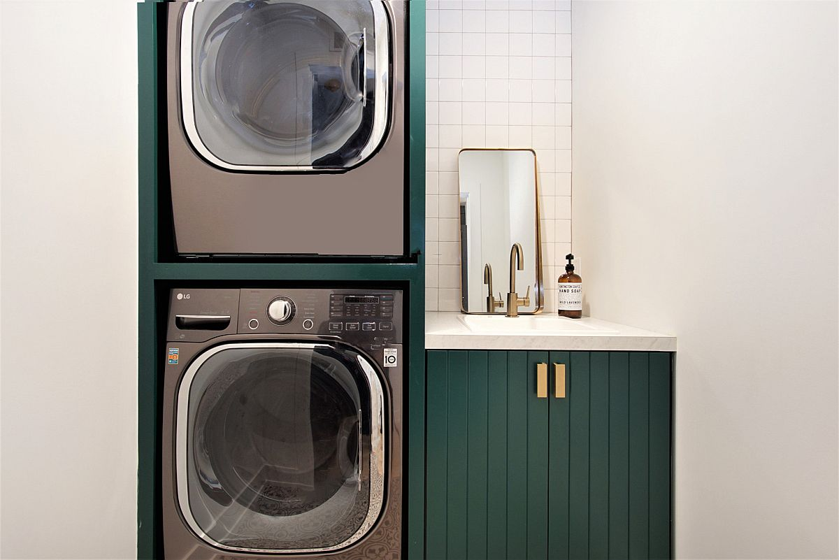 dark green cabinets with gold accents to hold washer and dryer