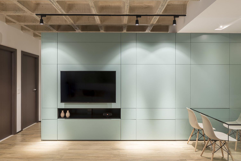 Track lightig inside the apartment highlghts the custom, colorful multitasking unit