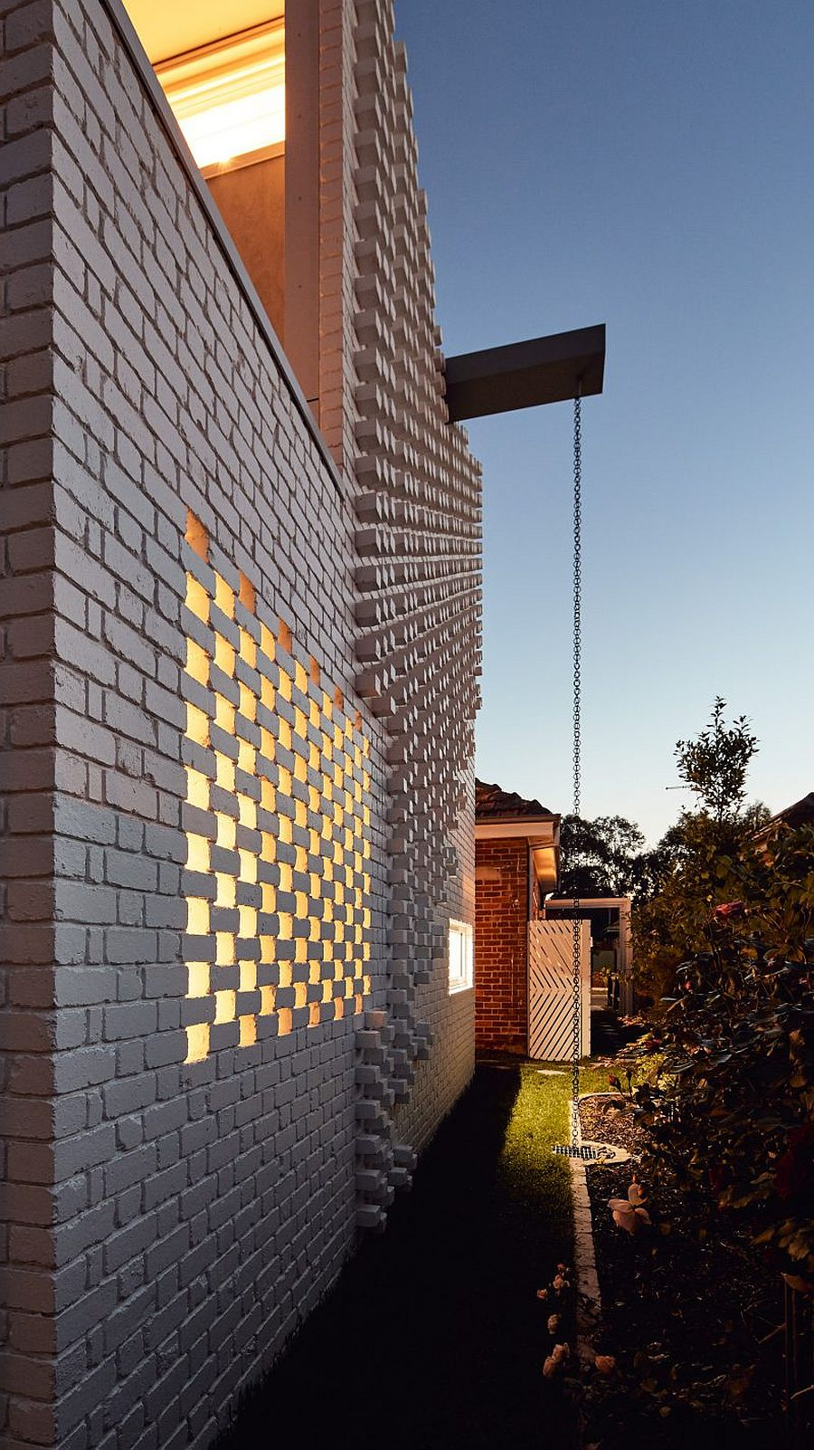 Unique brick wall extension with rain chain and other green features that make it planet-friendly