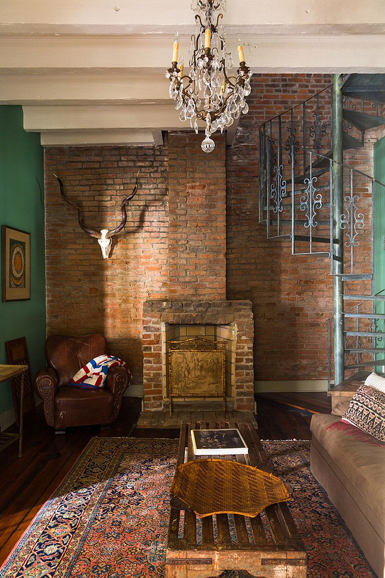 Unique brick wall in the backdrop with green on both sides for the eclectic living room