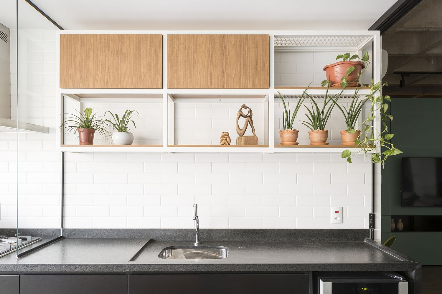 Wall in white tiles with greenery and small shelving in the kitchen