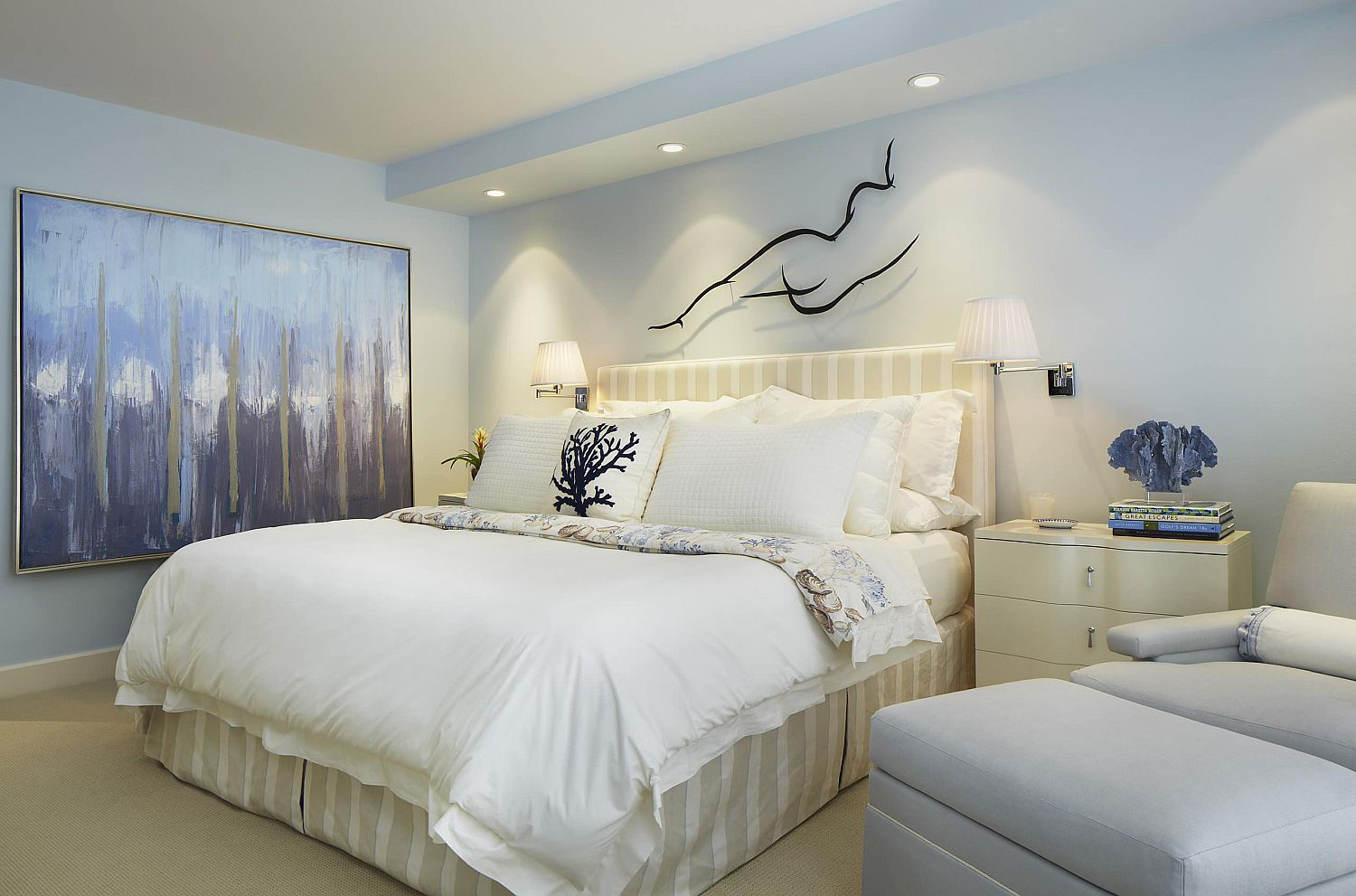 White and blue hues in the wall art elevate the crisp and neutral color palette of this bedroom