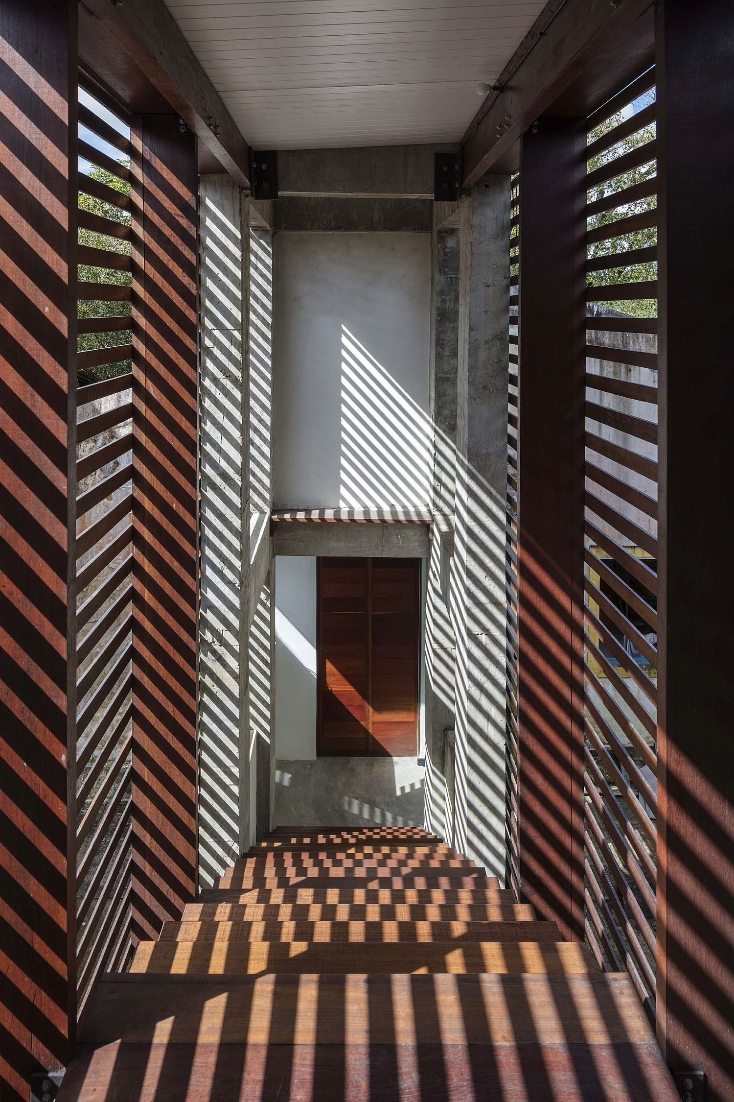 Wooden slats filter sunlight into the house