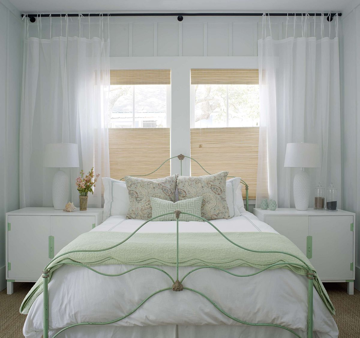 Wrought iron bed frame painted pastel green brings color to the chic bedroom in dreamy white