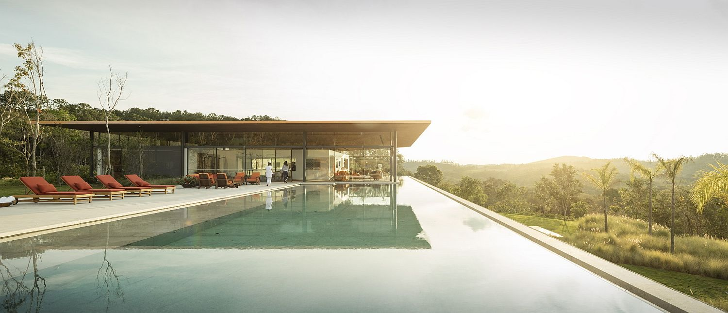 Stunning landscape and an infinity pool along with spacious deck next to it make this brazilian home even more special