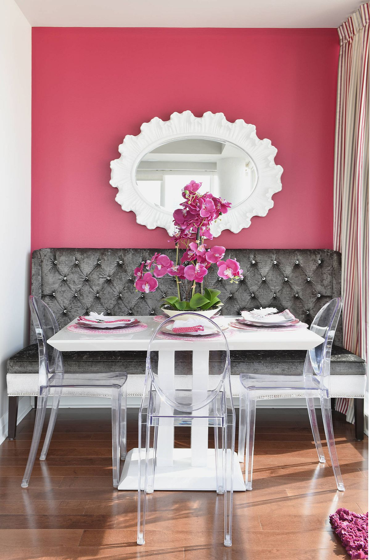 Banquette style dining room wth sofa-styled seating on one side and acrylic chairs on the other along with accent pink wall