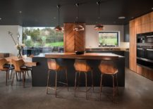 Chic-contemporary-bar-stools-along-with-sparkling-copper-pendant-lights-and-black-and-wood-kitchen-surfaces-217x155