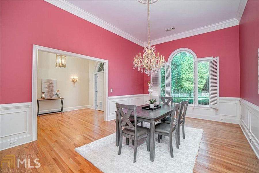 Classic pink and white dining room with whte window frames and ample natural light